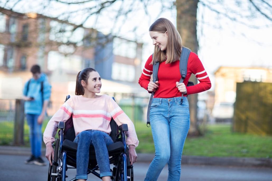 Zdjęcie ilustracyjne, dwie dziewczynki rozmawiają, jedna z nich jest na wózku inwalidzkim